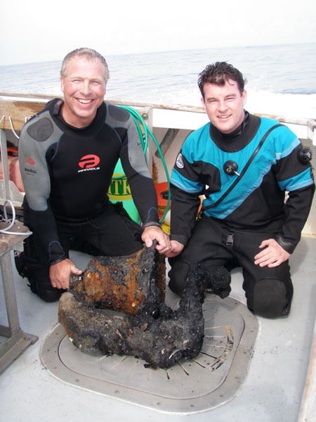 Divers who recovered the bell from the Proteus wreck display it on the deck of the Lion's Paw.